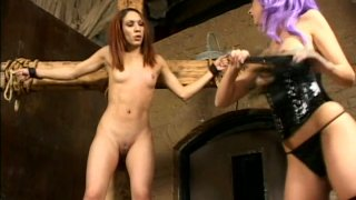 Skinny and sweet redhead girl is tied to hte cross for whipping